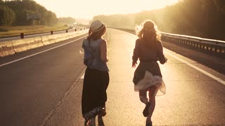 girl dressed in hippie-run on a lonely road in the rays of the rising sun. slow motion