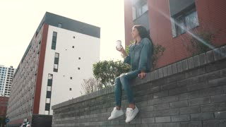 girl drinking coffee outdoors, sitting on the parapet