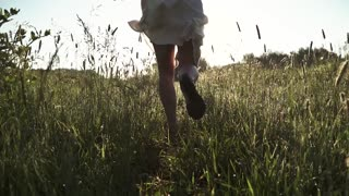 girl hippie runs across the meadow at dawn and sprinkles the dew. slow motion