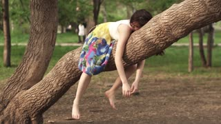 girl is very funny lying on the branch of a tree dangling down her arms and legs. beautiful girl dreaming in the Park lying on a tree branch. beautiful brunette smiling and laughing. slow motion