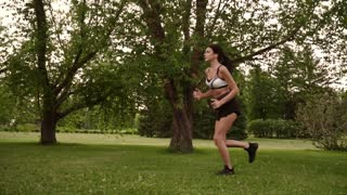 Girl jogging in the park. Young woman doing sports in nature. slow motion