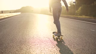 girl skates on an empty highway. Back view. slow motion