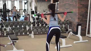 girl squats in the gym with a barbell