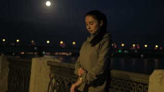 girl starts the training mode on a smart watches and begins jogging in the night city.