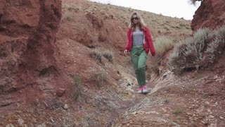 girl tourist in sunglasses goes on an unusual terrain. red mountains and red earth as on Mars.