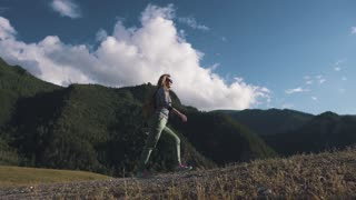 girl traveler in the background of mountains and clouds. A tourist with a backpack rises uphill.