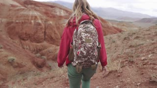 girl traveler with a backpack walking along the mountainous terrain. back view. red mountains and red earth as on Mars.