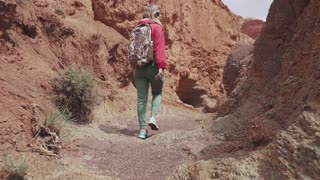 girl travels along an unusual terrain. red earth and mountains, like on Mars