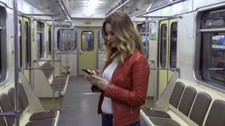 Girl with mobile phone in subway car