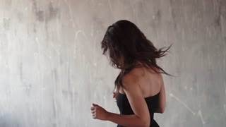 girl with the nice smile in a black dress smiling and looking into the camera. young woman with evening makeup. slow motion