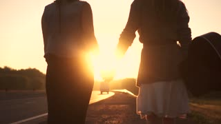 girlfriend go on the road in the rays of the rising sun and holding hands