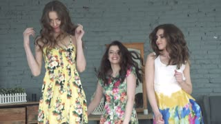 Girlfriends are having fun and jumping on the bed. Three beautiful young girls in dresses rejoice. slow motion