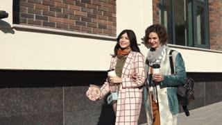 girlfriends for a walk. two young beautiful women are walking around the city holding coffee.