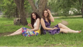 Girlfriends in a summer park sitting near a tree on the grass. Two good-looking girls spend time together, laugh, smile, have fun.