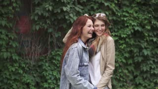 girlfriends laugh and hug. two beautiful redhead girls smiling and posing for the camera. 20s