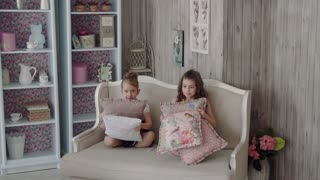girlfriends sitting on the sofa and throw pillow. little girls sisters playing sitting on the couch. slow motion