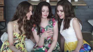 Girlfriends spend time together. Girls laugh watching photos on mobile phone.
