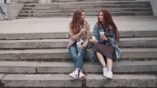 girls eating fast food sitting on steps in city