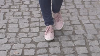 Girls feet in sneakers walking on the sidewalk