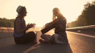 girls hippie sing songs and you play the guitar. two hipsters sitting on the roadway at sunset