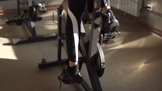 girl's legs close-up. The sportswoman turns the pedals on an exercise bike in the gym.