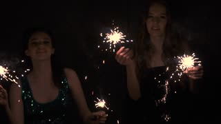 Glamorous and sexy girls dancing at a party with sparklers in hands