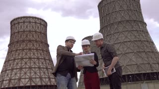 group of architects discussing a construction plan on the background of Cooling tower of nuclear power plant. coal-burning power plant . designers in construction helmets.