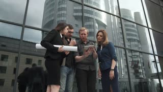 Group of businessmen background a modern office building. The manager shows the project on the screen of the tablet computer