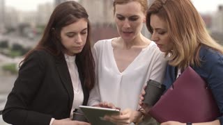 group of businesspeople talking and show each other the information on the screen of the tablet PC. three girls hold a business meeting in an informal setting on the roof of an office building