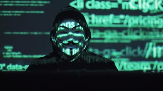 hacker in the mask hacks the program. the digital extortion gets access to other people's information. computer virus attack. binary codes projections and animation in background