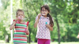 Happy child blowing soap bubbles in spring park. Two little girls have fun in the summer park. Slow motion