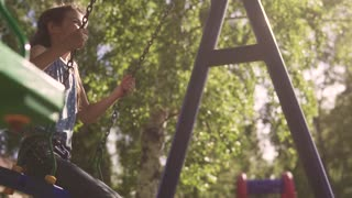 happy child swinging on a swing and laughing. joy and happiness of summer days. slow motion
