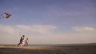 happy family launches a kite at sunset. early spring on the sea. children spend time with parents outdoors. Father, mother and two daughters on a picnic. slow motion
