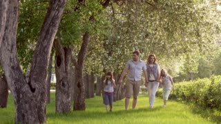 happy family walking in summer Park near the blossoming Apple trees. father, mother and two daughters spend time together outdoors at sunset. Children hold hands of their parents