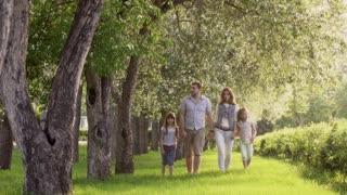 happy family walking in summer Park near the blossoming Apple trees. father, mother and two daughters spend time together outdoors at sunset.
