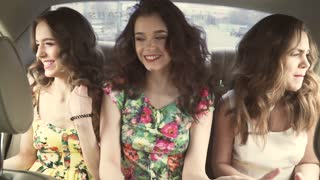 Happy girlfriends having fun in car going in vacation singing. young hipster couple dancing and singing like crazy in car driving. slow motion