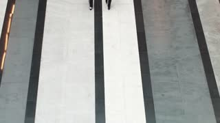 Head and assistant in an office building. two business women walking along the corridor of the business center. view from above
