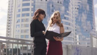 informal meeting of business partners on the background of the business center. two business women in formal suits talking outdoor