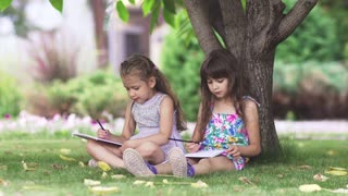 kids paint sitting on the grass under a tree. two little girls draw with crayons in the back yard