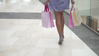 legs of a shopaholic girl close-up. happy and satisfied young woman walking with shopping bags for the shopping center. good shopping