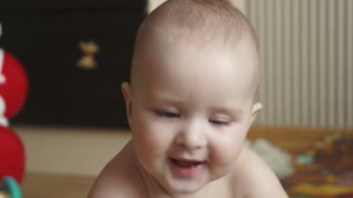 little baby 1 year old close-up. child lies on the floor of the house. little boy looks at camera and smiles