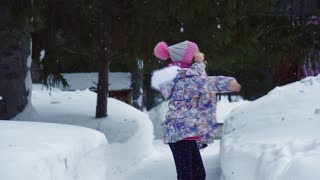 Little beautiful girl enjoys a walk through the winter forest. slow motion