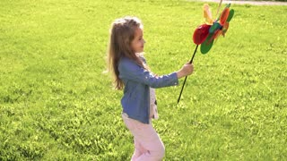 Little beautiful girl with toy in hands. The child is walking on the grass in a meadow.