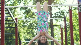 little funny girl hanging upside down on the horizontal bar.