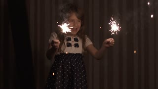 Little girl at holiday is happy and smiling holding in hands sparklers