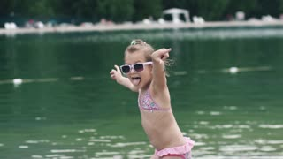 little girl fooling around and makes funny faces. the child bathing in the lake and enjoys a hot summer day. Slow motion