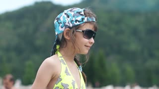 little girl in sunglasses and bathing suit smiling and posing for the camera. kid on vacation by the water. Slow motion