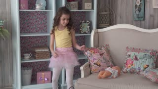 Little girl is playing at home with a doll and is rolling her in a stroller