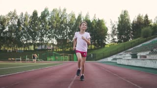 little girl jogging in the stadium. the child goes in for sports in the open air. children's sport.