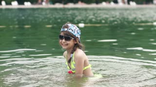 little girl playing in the water. baby having fun and splashing in river water. Slow motion